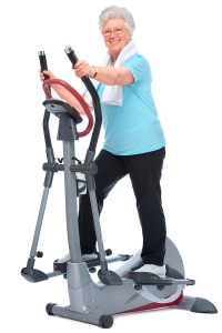 Attractive senior woman at health club, exercising on stepper
