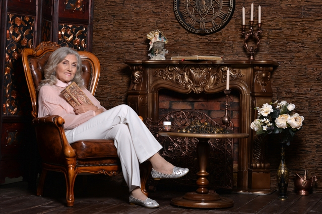 Portrait of beautiful elderly woman posing in room with vintage furniture